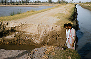 Two men standing by country road broken next to canal in rural Pakistan 1962