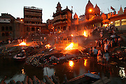 Bodies arrive day and night from far and near to be cremated at Jalasi Ghat, the cremation grounds at Manikarnika Ghat, Varanasi, India. One hundred or more times a day male family members carry a loved one's body through the narrow streets on a bamboo litter to the Ganges River shore?a place of pilgrimage for Hindus during life, and at death. Not every Hindu can be cremated here, because of transportation costs and logistical considerations. Sometimes a body is burned in one location and the ashes brought to Varanasi.