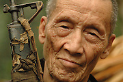 80 year old, Blia Yang Fang, holds his battered American made AR-15 he used as part of the CIA Secret Army, near Vang Vieng Laos, July 3, 2006..  He fought for the French when they held Laos as a colony and later fought for the CIA working in demolition teams to sabotage the North Vietnamese Army invading Laos...**EXCLUSIVE, no tabloids without permission**  .Pictured are a group of Hmong people who report an attack against them April 6, 2006 by Lao and Vietnamese military forces.  26 people perished, 5 were injured, and 5 babies died shortly after because their dead mothers could not breast-feed them.  Only one adult male was killed, the other 25 victims were women and children (17 children).  The Lao Spokesman for the Ministry of Foreign Affairs says this is a fabrication, an investigation has been completed, and there was no attack.  The Hmong group says no officials have interviewed witnesses or visited the crime scene, a point the Lao Spokesman did not deny.  ..The Hmong people pictured have hidden in remote mountains of Laos for more than 30 years, afraid to come out.  At least 12,000 are said to exist, with little food, scavenging in the jungle. Most have not seen the modern world.  Since 1975, under the communists, thousands of reports evidence the Hmong have suffered frequent persecution, torture, mass executions, imprisonment, and possible chemical weapons attacks.  Reports of these atrocities continue to this day.  The Lao Government generally denies the jungle people exist or that any of this is happening.  The Hmong group leader, Blia Shoua Her, says they are not part of the Hmong resistance and want peace.  He claims they are just civilians defending their families, hoping to surrender to the UN..