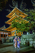 """Two women in kimonos consult smartphones under the three-storied Koyasu Pagoda which is lit at night. Kiyomizu-dera (""""Pure Water Temple"""") is an independent Buddhist temple in eastern Kyoto, Japan. Otowa-san Kiyomizu-dera temple is part of the Historic Monuments of Ancient Kyoto (Kyoto, Uji and Otsu Cities) UNESCO World Heritage site. Kiyomizu-dera was founded on the site of the Otowa Waterfall in the early Heian period, in 780 by Sakanoue no Tamuramaro. Ordered by Tokugawa Iemitsu, its present buildings were built entirely without nails in 1633."""