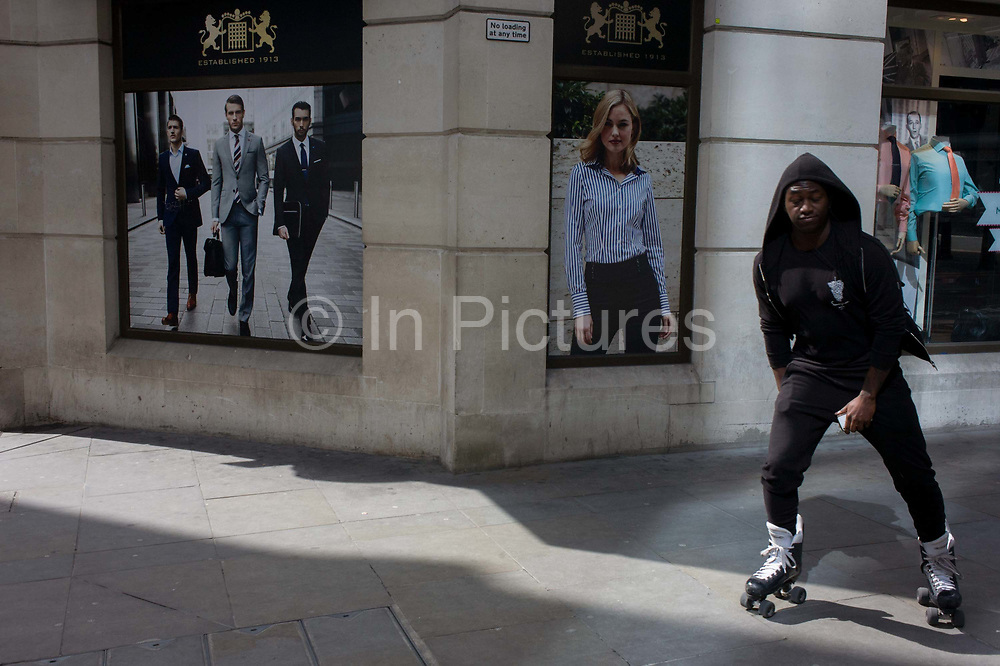 Man on skates glides past a stylish clothing shop for business people on a poster in the City of London. Skating past the images of very good-looking and stylish men wearing sharp suits - the latest in 2015 city fashion - the youth looks out of place from an otherwise white and elite class of young people. The street is in the City of London, the capital's financial heart.