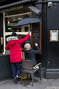 Sheltered by an umbrella held above her head, a woman signwriter artist paints the text of a West End pubs food menu of pies and fish & chips, outside The Porcupine, a traditional British pub on Charing Cross Road, on 17th February 2020, in London, England.