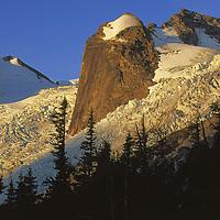 A glacier wraps around a rock formation.