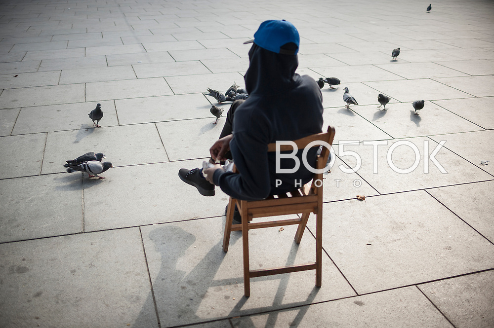 An African migrants feeding pigeons in the main square. Irun (Basque Country). October 23, 2018. A group of volunteers has created a host network to serve migrants and inform about the public services they are entitled to and the ways to cross the border. This group of volunteers is avoiding a serious humanitarian problem Irun, the Basque municipality on the border with Hendaye. As the number of migrants arriving on the coasts of southern Spain incresead, more and more migrants are heading north to the border city of Irun. French authorities have reacted by conducting random checks as far as the city of Bordeaux, more than 200 kilometers north of the border. Migrants who are caught are then deported back to Irun. (Gari Garaialde / Bostok Photo).