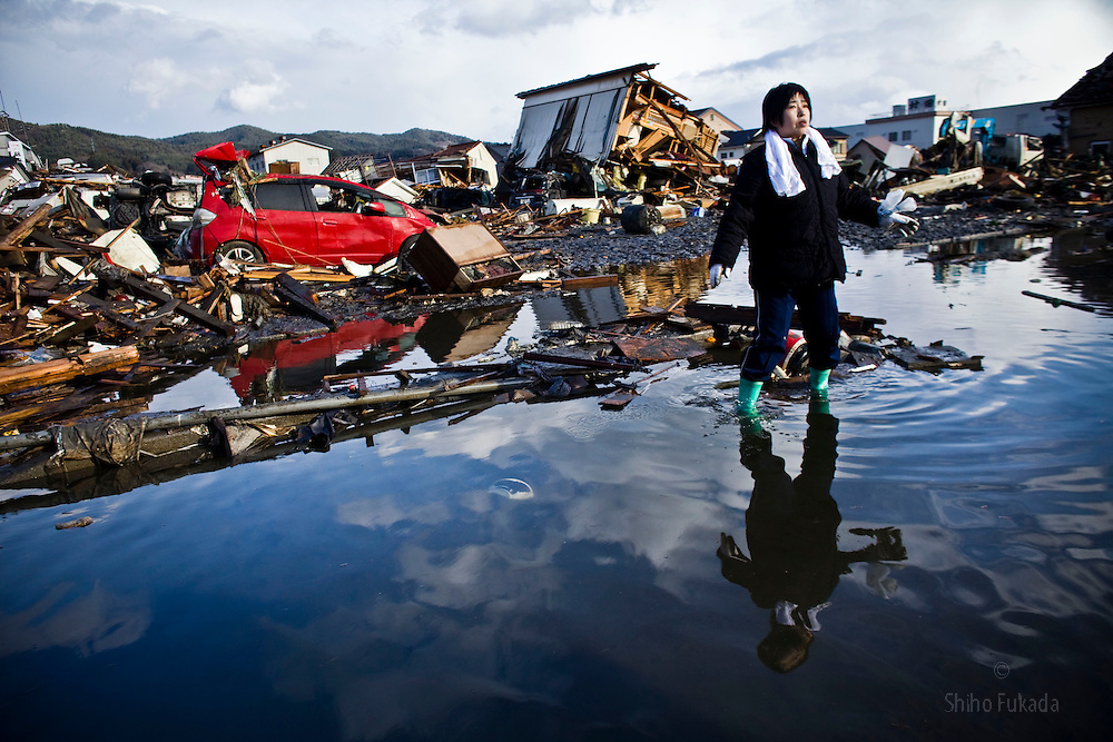"""Chieko Chiba looks for remains of her house in Kesennuma, Miyagi prefecture, Japan, March 16, 2011. """"Everything is gone.""""  she said."""