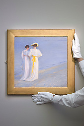 © Licensed to London News Pictures. 16/11/2012. London, UK. A Sotheby's employee holds 'Summer Evening on Skagen's South Beach' (1893) (est. GB£150,000-250,000), an oil study by Danish artist Peder Severin Kroyer, at a press call taking place at the London based auction house's New Bond Street premises today (16/11/12).  The sale, featuring works by 19th century European painters, is set to take place on the 20th of November. Photo credit: Matt Cetti-Roberts/LNP