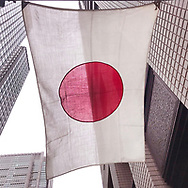 """April 30, 2019, Tokyo, Japan: A Japanese flag billows in the wind in the Otemachi business district nearby Japan's Imperial Palace. This was on the final day of the reigning Japanese Emperor Akihito and the last day of Japan's Heisei Era which spanned from 1989 to April 30, 2019. Traditionally Japanese calendars years are based upon the years of emperor's reigns. The new era has been called 'Reiwa"""" era which starts on May 1, 2019 when Crown Prince Naruhito ascends to the throne."""