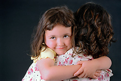 Young girl being carried by mother; looking over her shoulder smiling,