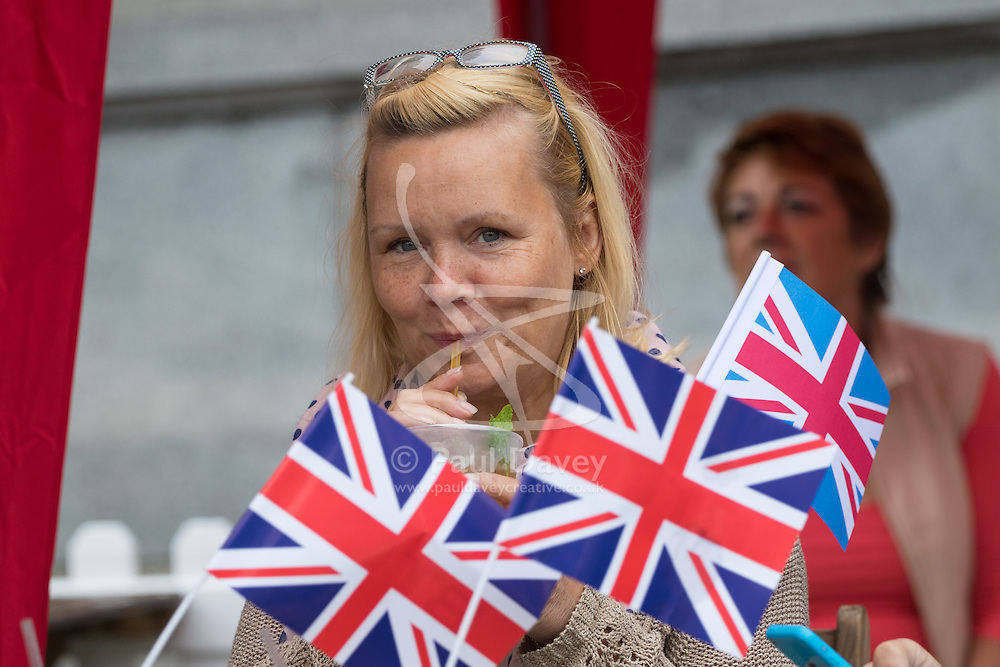 Trafalgar Square, London, June 12th 2016. Rain greets Londoners and visitors to the capital's Trafalgar Square as the Mayor hosts a Patron's Lunch in celebration of The Queen's 90th birthday. PICTURED: A woman takes a sip of PIMMS as the rain eases off.