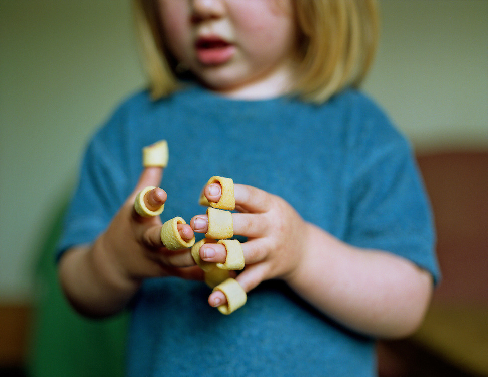 A three year old child eating potato rings from her fingers.