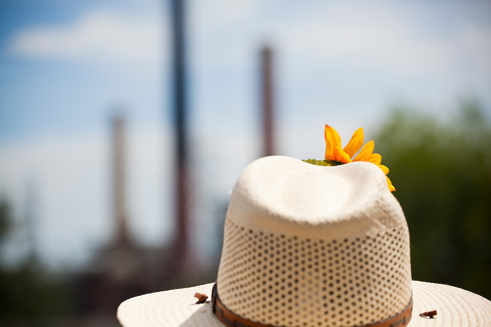 An activist wearing a Coloradowboy hat and sunflower looks out towards the coal-fired Valmont Power Plant in Boulder, Colorado during a protest of its continued operation.