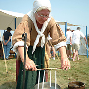 August 25, 2007 -- PHIPPSBURG, Maine.  Mary Muckenhoupt makes candles by dipping at the celebration of the 400th anniversary of the Popham Colony on Saturday. Candles were made in this fashion in the 17th century, using tallow and other  methods. Mary adds modern materials to improve burning time and aid with durability. .Muckenhoupt is a member of The Society of the 17th Century, an organization of 17th and 18th Century re-enactors. The group set up at Popham in order to provide a sense of what life might have been like in the Popham Colony -- which was founded in 1607 in present day Phippsburg. While the colony lasted less than a year, it was one of the first steps towards establishing permanent settlements of Europeans in North America. Photo by Roger S. Duncan.