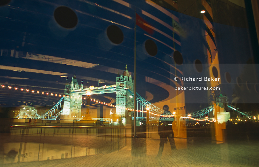 Looking through the large windows of Greater London Mayor (GLA) Ken Livingstone's headquarters on the River Thames, a lone figure stands silhouetted with a floodlit Tower Bridge in the background. We see the reflections of the GLA building pasted over the evening sky above Tower Bridge. London's famous bridge was completed in 1894 and remains one of the capital's most visible symbols both for Victorian engineering and as a tourist landmark. The Mayor's Greater London Authority (GLA) headquarters stands over the Thames, opposite the Tower of London on the north shore.