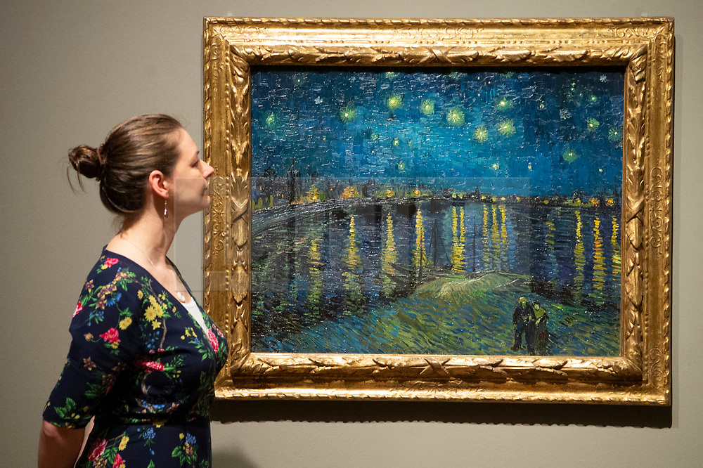 © Licensed to London News Pictures. 25/03/2019. A Tate member of staff views a painting titled Starry Night (1888) by artist Vincent van Gogh. The painting is part of The EY Exhibition: Van Gogh and Britain at the Tate BritainLondon, UK. Photo credit: Ray Tang/LNP