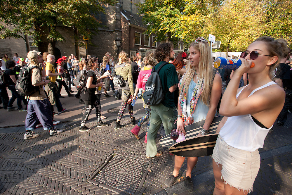 Twee meisjes met een skateboard kijken ietwat verbaasd naar een demonstratie. Meer dan duizend mensen lopen en dansen mee met de streetrave in Utrecht. De Utrechtse kraakbeweging wilde op een positieve manier laten weten het niet eens te zijn met het kabinetsbeleid. De naam van de tocht, Partijtje van de Vrijheid, refereert aan de PVV.<br /> <br /> More than thousand people are dancing and demonstrating in Utrecht. Organized by squatters in Utrecht, they want to protest against the Dutch government in a positive way.