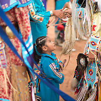 Ariel Cachini looks up at the fellow dancers surrounding her at the Zuni Fairgrounds Friday.