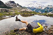 Yoav Bar-Ness lies down on the ground to photograph reflections of Mount Baker in an alpine tarn above Lake Ann, North Cascades National Park, Washington.