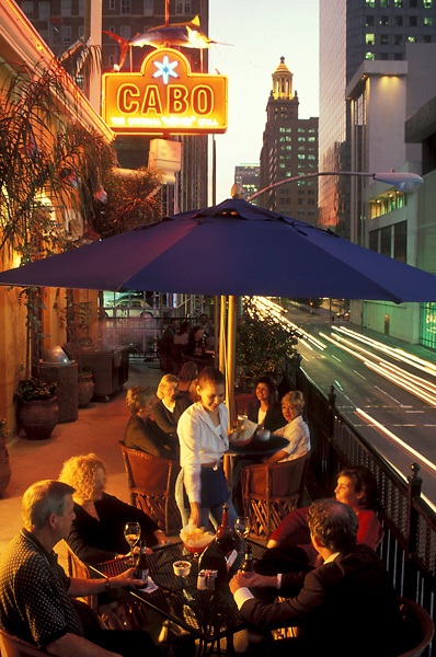 Stock photo of groups dining under umbrellas on the outdoor patio at Cabo in downtown Houston Texas