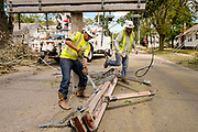 18 AUGUST 2020 - CEDAR RAPIDS, IOWA: IBEW electrical workers take apart a destroyed power pole in Cedar Rapids. Cedar Rapids was the state's hardest hit city by the derecho that roared across Iowa last week. City officials said the damage left by the derecho was more extensive than the 2008 flood that destroyed much of its downtown. City residents are reporting that almost every home was damaged in the storm, many businesses were closed, and up to half of the city's tree canopy was destroyed. A week after the storm, more than 40,000 homes were still without power. A spokesman for Alliant Energy said the utility has replaced as many power poles in one week that they normally replace in 8 months. On Monday, President Trump approved a $4 billion emergency declaration for Iowa to aid in derecho recovery.    PHOTO BY JACK KURTZ