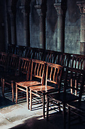 Two seats in a church with sunlight upon them.