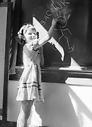 "0003-014. Girl drawing ""Teachur"" stick figure on chalkboard. Evaline Elementary school, near Winlock, Washington. The photographer, Stuart Fresk, was a teacher there from 1935 to 1946."