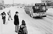 Passengers catch the Hop at a bus stop on Canyon Street in winter in Boulder, Colorado.