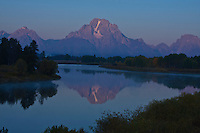 Reflections of 12,605 ft. Mount Moran in Oxbow Bend at sunrise.  The smoky haze is caused by a near by wild fire.  Grand Teton National Park, Wyoming, USA.