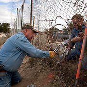 Bob Maupin has lived on the U.S./Mexico border for over 60 years in eastern San Diego County. His fence abuts Mexico and is often used by migrant and drug smugglers to illegally enter the United States. Much of Bob's day, including Inauguration Day on January 20, 2009, is devoted to checking his fence and property for signs of illegal entry. Here, neighbor Dick Buck, right, a Minuteman Civil Defense Corps volunteer, helps Bob repair the fence cut by smugglers. Please contact Todd Bigelow directly with your licensing requests.