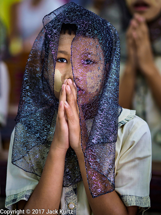 19 NOVEMBER 2017 - HWAMBI, YANGON REGION, MYANMAR: Girls at mass in Sacred Heart's Catholic Church in Hwambi, about 90 minutes north of Yangon. Catholics in Myanmar are preparing for the visit of Pope Francis. He is coming to the Buddhist majority country November 27-30. There about 500,000 Catholics in Myanmar, about 1% of the population. Catholicism was originally brought to what is now Myanmar more than 500 years ago by Portuguese missionaries and traders.    PHOTO BY JACK KURTZ
