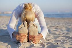 March 17, 2014 - Woman doing yoga prayer stretch on the beach (Credit Image: © Image Source/Image Source/ZUMAPRESS.com)