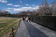Washington, DC, USA -- February 14, 2020. A  wide angle photo of visitors walking by the Vietnam Veterans Memorial on a clear winter day.
