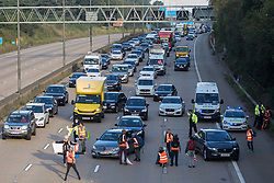 Insulate Britain climate activists begin to block the anticlockwise carriageway of the M25 between Junctions 9 and 10 as part of a campaign intended to push the UK government to make significant legislative change to start lowering emissions on 21st September 2021 in Ockham, United Kingdom. Both carriageways were briefly blocked before being cleared by Surrey Police. The activists are demanding that the government immediately promises both to fully fund and ensure the insulation of all social housing in Britain by 2025 and to produce within four months a legally binding national plan to fully fund and ensure the full low-energy and low-carbon whole-house retrofit, with no externalised costs, of all homes in Britain by 2030.