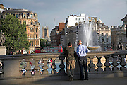 Two men looking over Trafalgar Square, London, England Fountain,