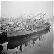 """ackroyd-P171-11. """"SS Red Oak Victory. February 10, 1966"""" (at Northwest Marine Iron Works on Swan Island. They had a contract for drydocking , bottom work, opening up lines and machinery preparation - see Oregonian January 21, 1966 pg. 42). (USS Red Oak Victory (AK235), commissioned in December, 1944, is the only World War II Victory Ship built by the Kaiser Shipyards that is restored. The ship saw service in World War II, Korea and Vietnam. In 1996, by an Act of Congress, title to the SS Red Oak Victory was conveyed to the Richmond Museum Association (Richmond Museum of History).  (Ship discharging oily waste into river.)"""
