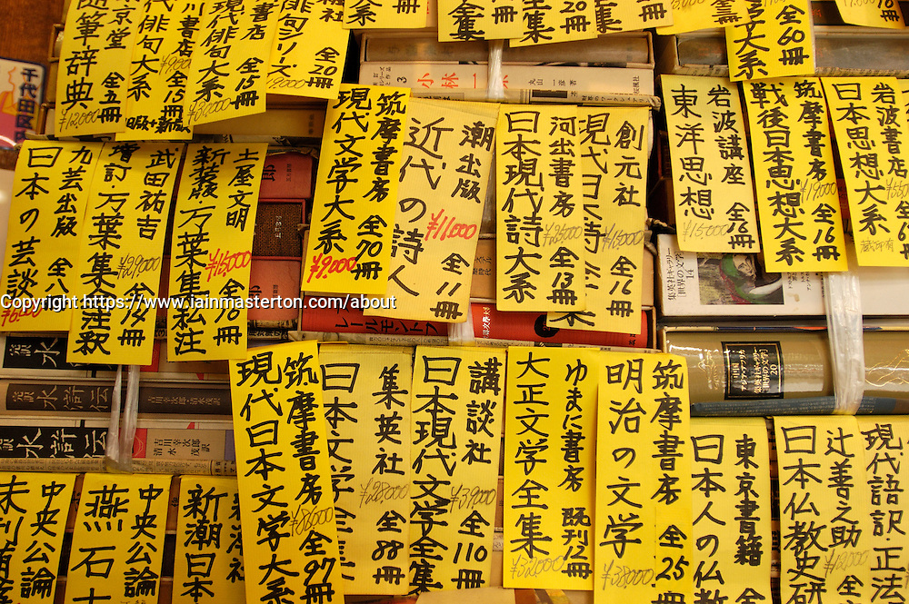 Detail of yellow labels on old books in secondhand bookshop in Jimbocho bookshop district of Tokyo Japan