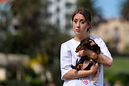 A woman holds her sausage dog at St Kilda Beach during COVID-19 in Melbourne, Australia. Premier Daniel Andrews comes down hard on Victorians breaching COVID 19 restrictions, threatening to close beaches if locals continue to flout the rules. This comes as Victoria sees single digit new cases. (Photo by Dave Hewison/Speed Media)
