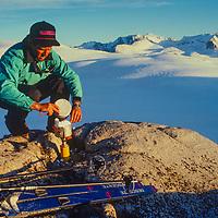 A Ski Mountaneers prepares a stove for evening meal near  Paiute Pass in the John Muir Wilderness, Sierra Nevada, California
