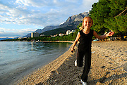 Child (9 years old) running along beach in late afternoon sun, with the Biokovo National Park, part of the Dinaric Alps, in the background. Makarska, Croatia