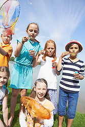 Children blowing bubbles with bubble wands, Bavaria, Germany