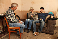 Teenager with grandparents looking at newspaper for jobs