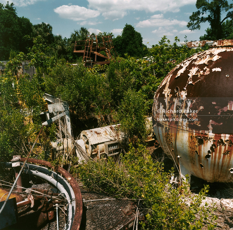 NASA Space Junk Auction.Gantries and tracking equipment in the wasteland..Rocket gantries and tracking equipment left to rust in the back yard of NASA scientist Charles Bell. Assorted rocket paraphenalia. At the very back of the auction site, a whole jungle of Apollo and Shuttle junk was buried in the undergrowth having been forgotten there for decades. Here we see gantries and tracking (communications) structures.
