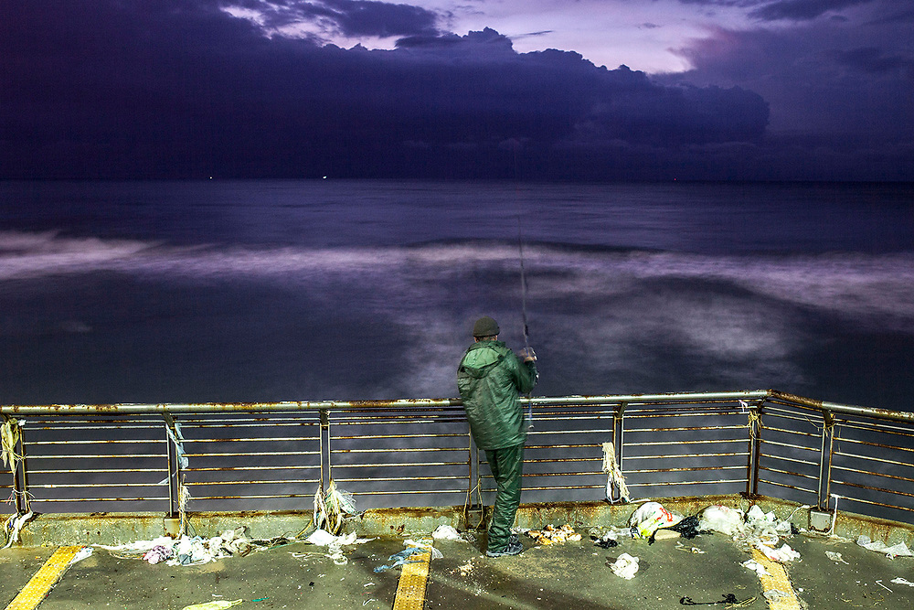 A fisherman is waiting to catch a fish, at the mediterranean coastal city of Netanya.