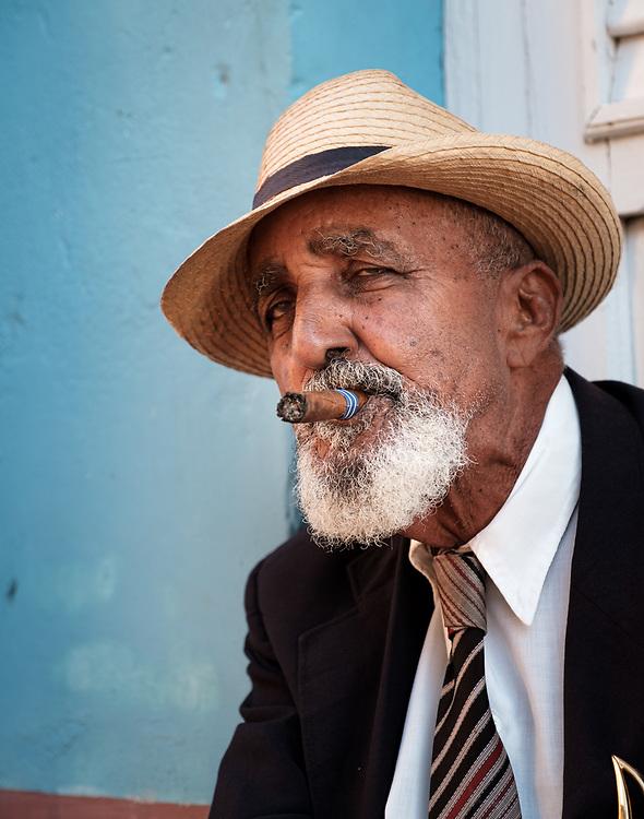 TRINIDAD, CUBA - CIRCA JANUARY 2020: Portrait of Cuban man in the streets of Trinidad smoking a cigar.