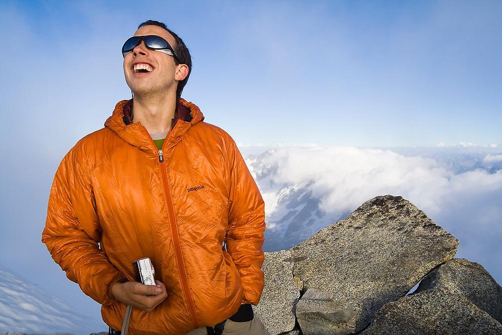 Brian Polagye looks up towards the sun standing on the summit of Eldorado Peak, North Cascades National Park, Washington.