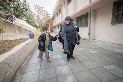 19 February 2020, Amman, Jordan: 10-year-old Bayan (left), a girl born with Cerebral Palsy, walks with her mother Eman Ahmed (right) to the Al Yarmouk Primary Mixed School, in the Lewa'a Al Jama'a district. Following three years in a school exclusively for children with disabilities, today Bayan attends 4th grade at Al Yarmouk, which has recently opened up to receive her. The school teaches some 750 students from 1st - 6th grade, most of them Jordanian, but some also from Syria and other countries. The school has received support from the Lutheran World Federation in refurbishing their buildings and classrooms, as well as training on protection and social cohesion, including how to become more inclusive of children with disabilities.