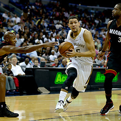 Oct 23, 2013; New Orleans, LA, USA; New Orleans Pelicans shooting guard Austin Rivers (25) drives past Miami Heat shooting guard Ray Allen (34) and shooting guard Dwyane Wade (3) during the first half of a preseason game at New Orleans Arena. Mandatory Credit: Derick E. Hingle-USA TODAY Sports