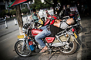 "A Chinese motorbike taxi driver takes a rest on his motorbike's seat in YangShuo near Guilin, China, August 01, 2014. <br /> <br /> This image is part of the series ""24/7"", an ironic view on restless and fast-growing Chinese economy described through street vendors and workers sleeping during their commercial daily activity. <br /> <br /> © Giorgio Perottino"