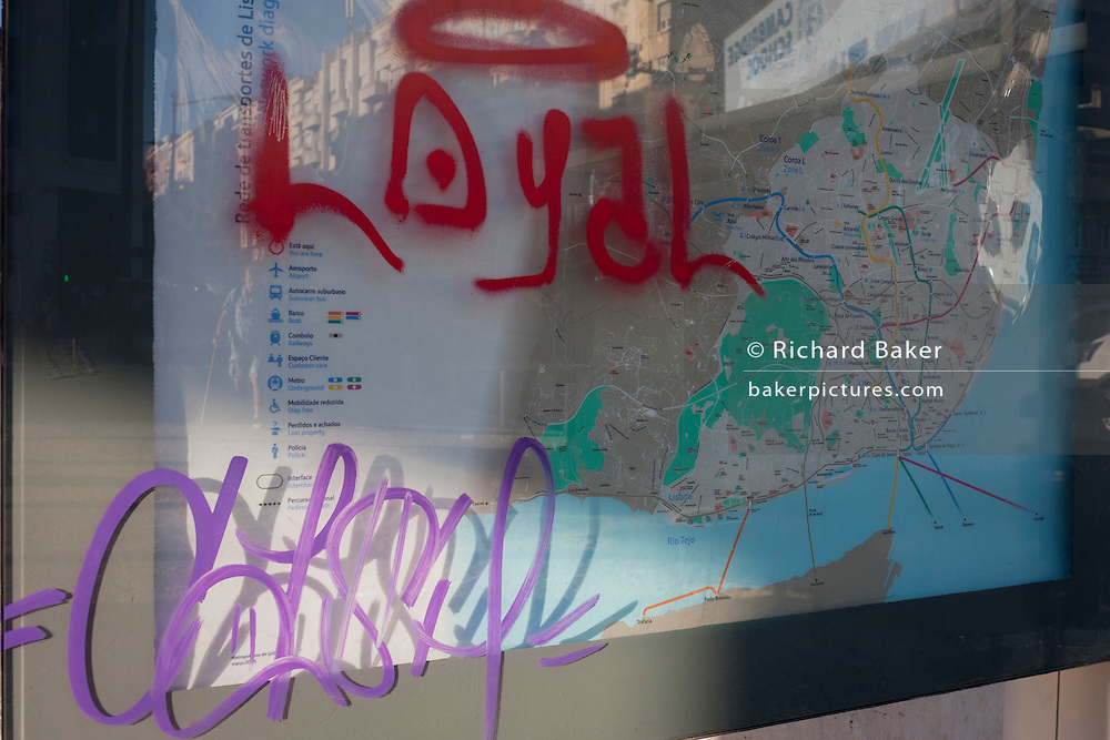 Graffiti partially covers a city map at Alameda metro station, Lisbon, Portugal.