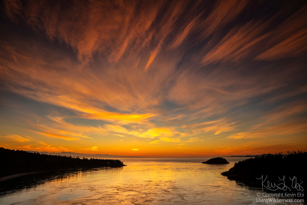 Wispy cirrus clouds become fiery after sunset over Deception Pass in Island County, Washington. Deception Pass is a strait that connects the Strait of Juan de Fuca with Skagit Bay, separating Whidbey (left) and Fidalgo (right) islands.