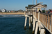 NC01397-00...NORTH CAROLINA - Fishermen with lines out from the deck of the concrete supported Jennettes Pier on the Outer Banks at Nags Head.